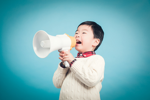 623763462 istock photo Boy with megaphone making an announcement 1135133583