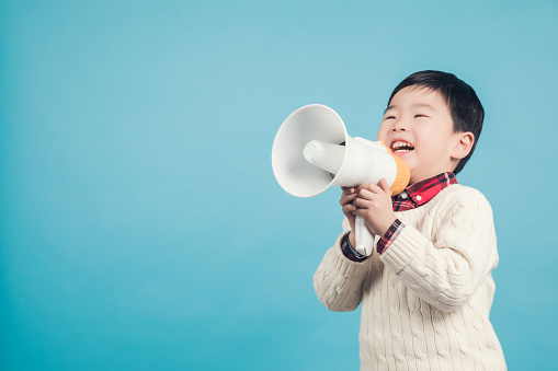 623763462 istock photo Boy with megaphone making an announcement 1135133589