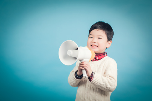 623763462 istock photo Boy with megaphone making an announcement 1135133603