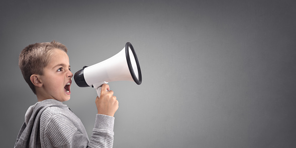 623763462 istock photo Boy with megaphone making an announcement 886661752