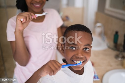 istock Boy with mother brushing teeth at home 800444456