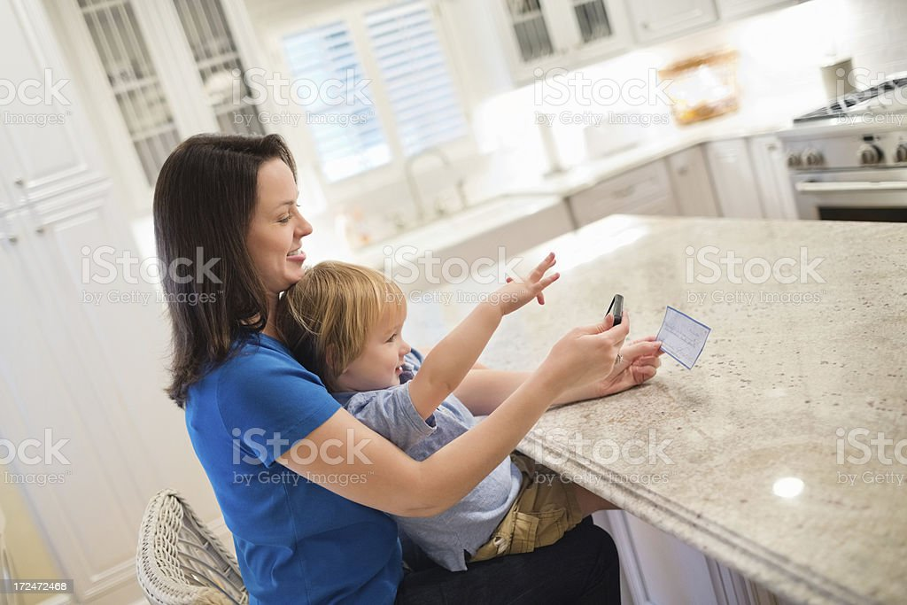 Boy With Mother Depositing Check Through Mobile Phone royalty-free stock photo