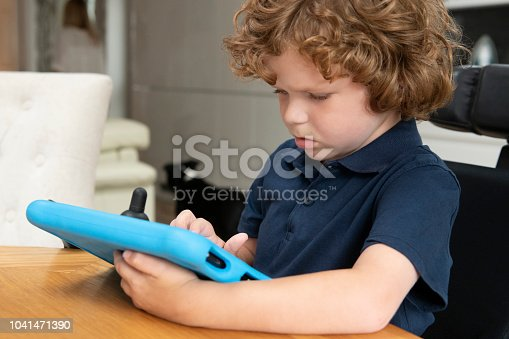 6 year old disabled boy holding and looking at mobile device at home, touching screen and concentrating