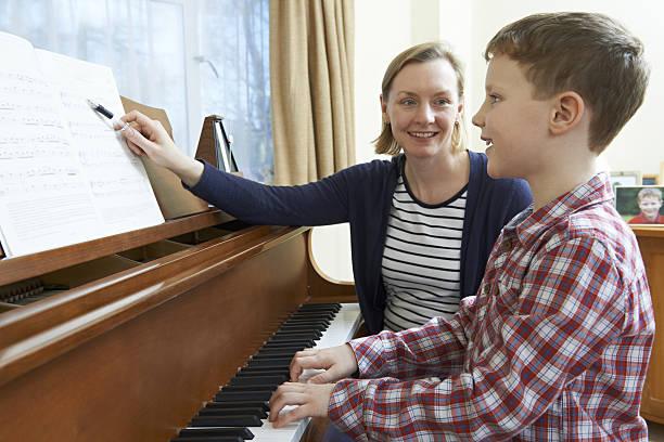 junge mit musik lehrer, die unterricht im klavier - piano noten stock-fotos und bilder