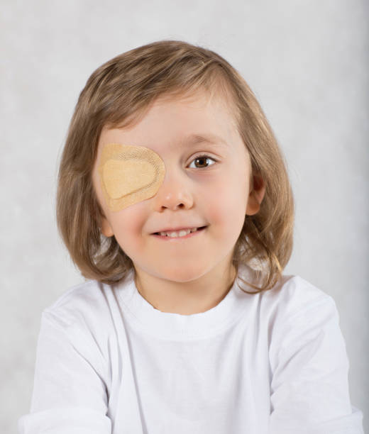 Boy with one eye covered by eye pad. stock photo