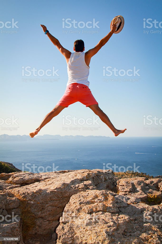 Boy with open arms jumping for joy celebrating freedom stock photo