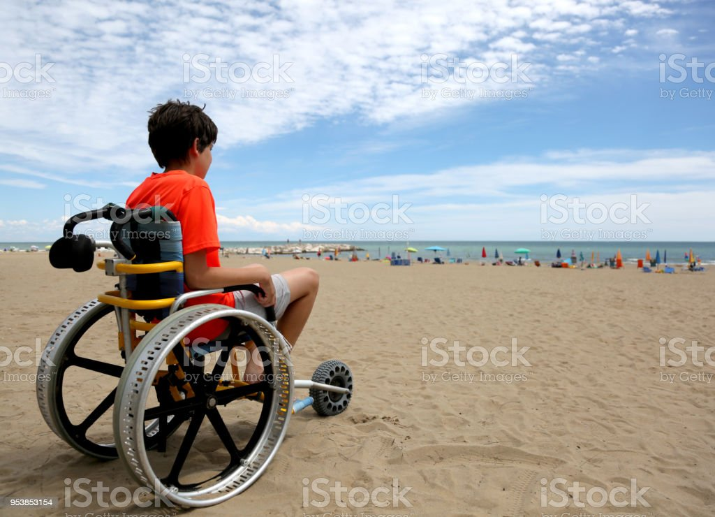 boy with orange t-shirt sitting on the wheelchair with aluminum stock photo