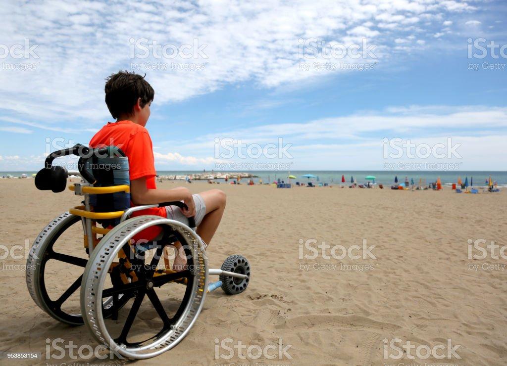 Turuncu tişört alüminyum ile tekerlekli sandalye üzerinde oturan çocukla stok fotoğrafı
