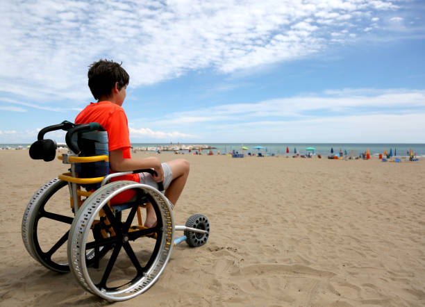 boy with orange t-shirt sitting on the wheelchair with aluminum boy on the special wheelchair with aluminum alloy wheels on the beach in summer amyotrophic lateral sclerosis stock pictures, royalty-free photos & images