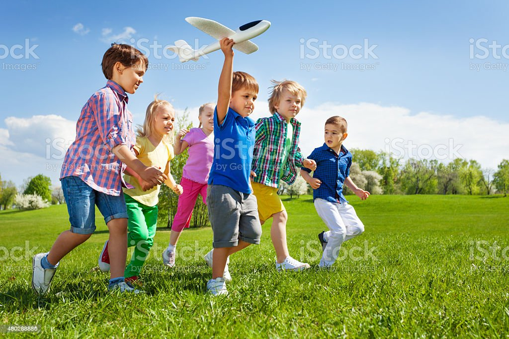 Boy with other kids runs and holds airplane toy stock photo