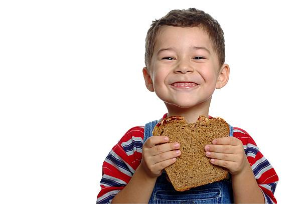 Boy with Peanut Butter and Jelly Sandwich on Whole Wheat A 5-year-old boy enjoying a peanut butter and jelly sandwich on whole wheat bread bib overalls boy stock pictures, royalty-free photos & images