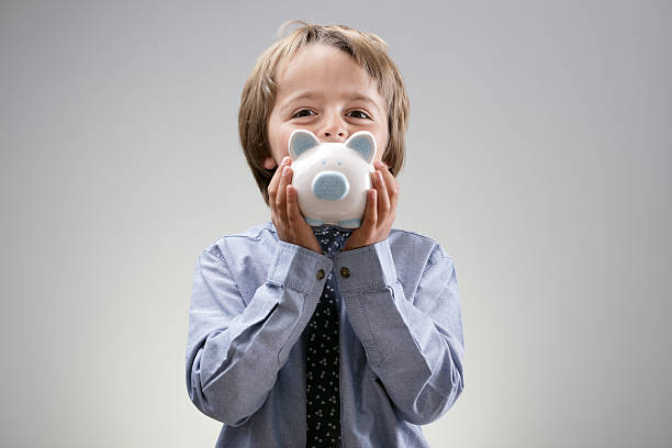 Boy with piggy bank Boy smiling and holding a piggy bank concept for savings, banking, finance or saving for an education allowance stock pictures, royalty-free photos & images