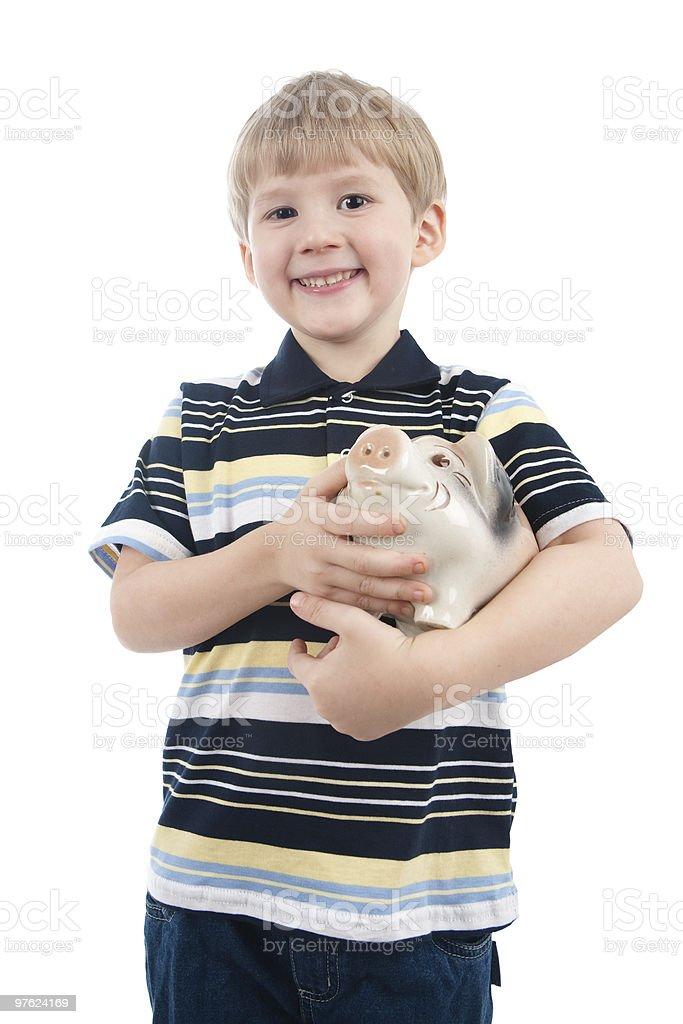 Petit garçon avec la tirelire cochon photo libre de droits