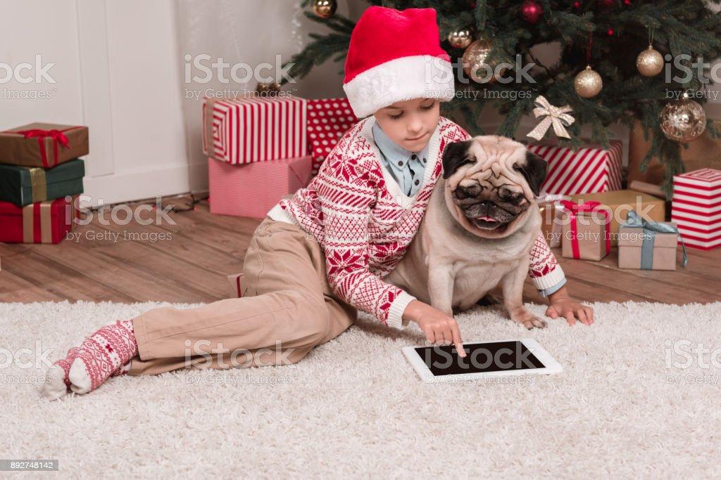 boy with pug using tablet on christmas stock photo