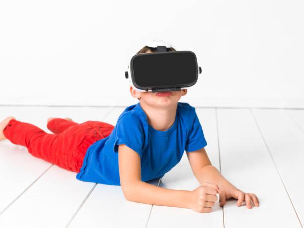 Junge mit roter Hose und blauem Hemd setzt virtuelle Brille zu Hause – Foto