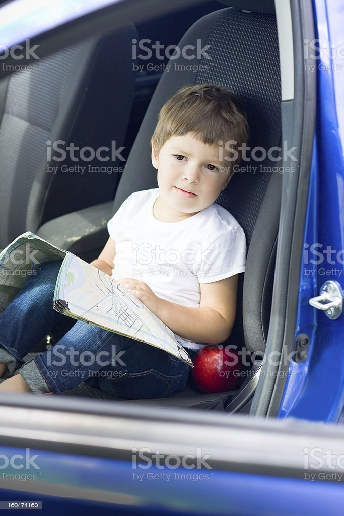 Boy with road map and apple sits in car royalty-free stock photo
