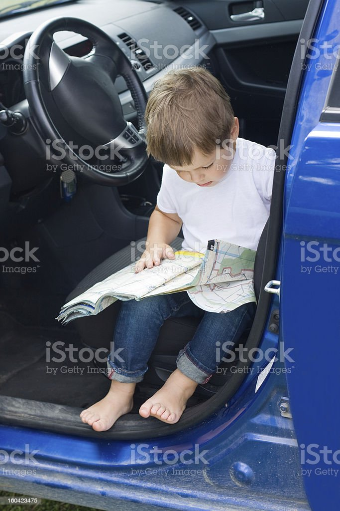 Boy with road map sits in car royalty-free stock photo