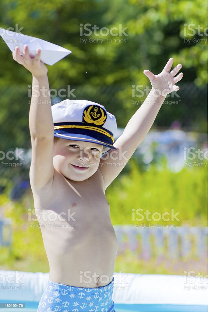 Boy with sailor cap an paper ship in swiming pool royalty-free stock photo