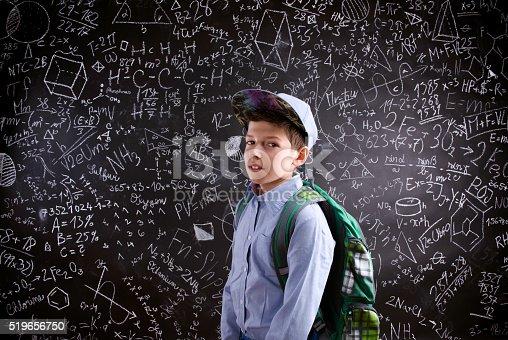 istock Boy  with schoolbag against big blackboard with mathematical sym 519656750
