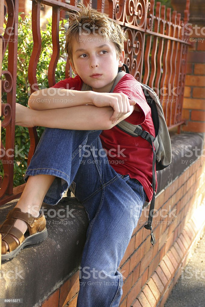 Boy with schoolbag slung over shoulder royalty free stockfoto