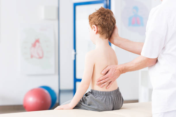 boy with scoliosis during rehabilitation - skoliose stock-fotos und bilder