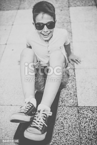 Photo of boy with skateboard on the street