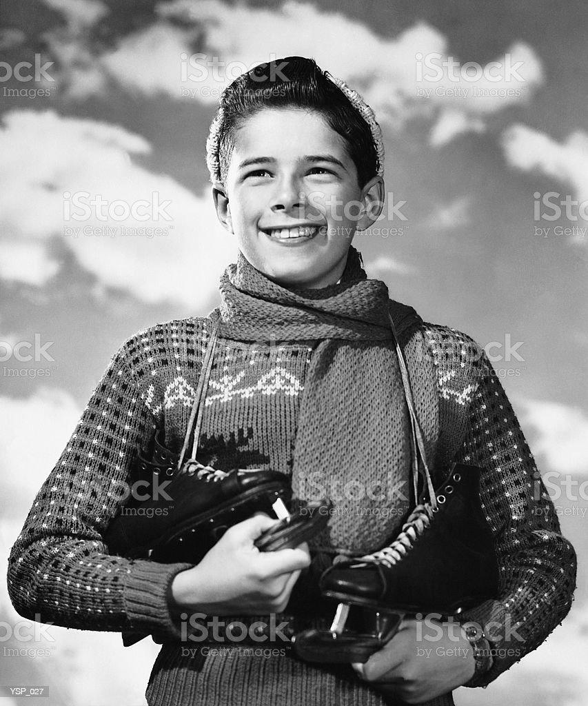 Boy with skates slung over his shoulder 免版稅 stock photo