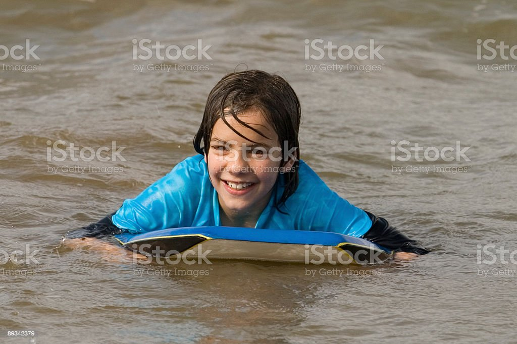 Boy with surf board off New Zealand beach stock photo