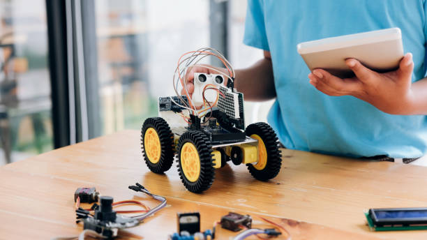 Boy with tablet pc computer programming electric toys and building robots. stock photo