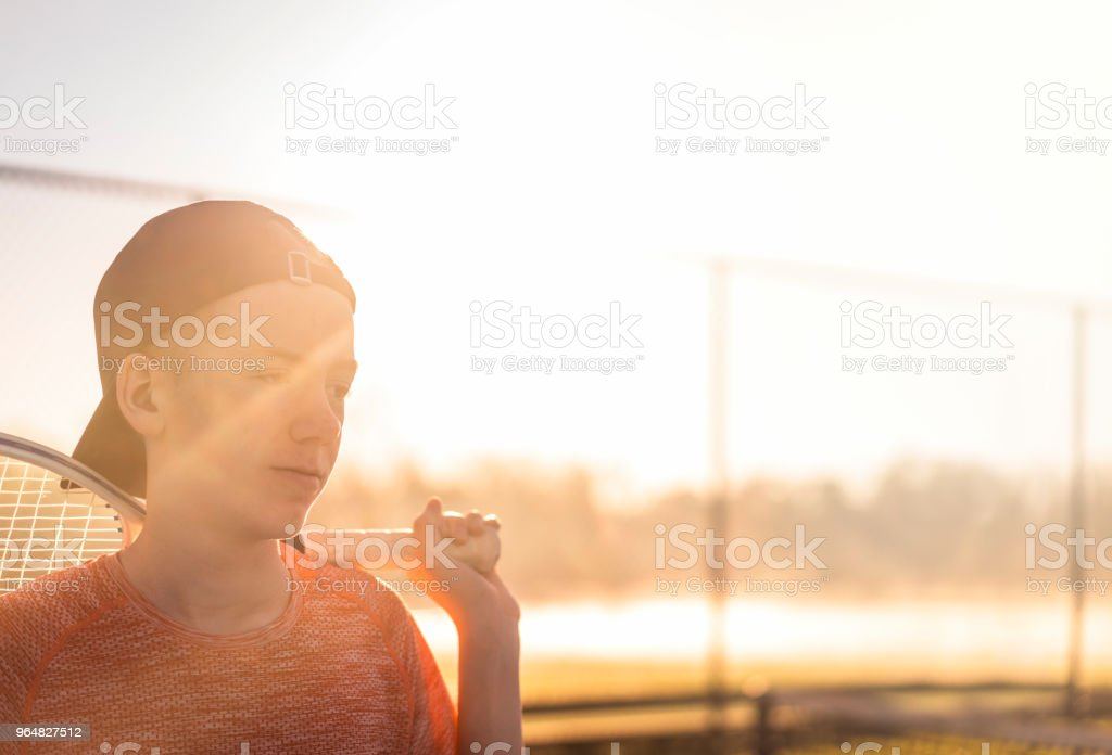 Boy with tennis racket looking away at court royalty-free stock photo