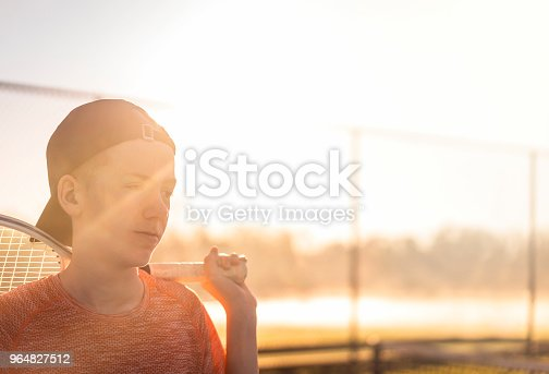 Teenage boy looking away while holding tennis racket at court. Confident male is in sportswear on sunny day. He is playing in city.