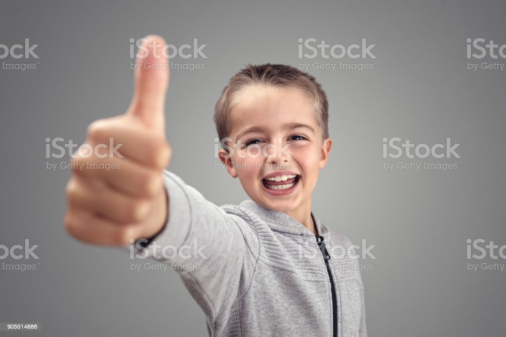 Boy with thumbs up agreeing stock photo