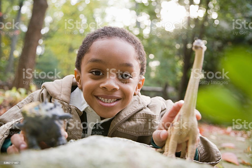 Boy with toy dinosaurs stock photo