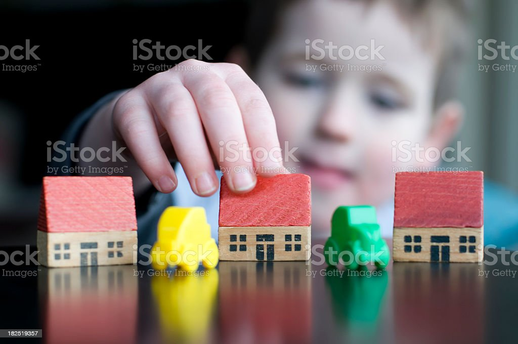 Boy with toy houses and cars stock photo