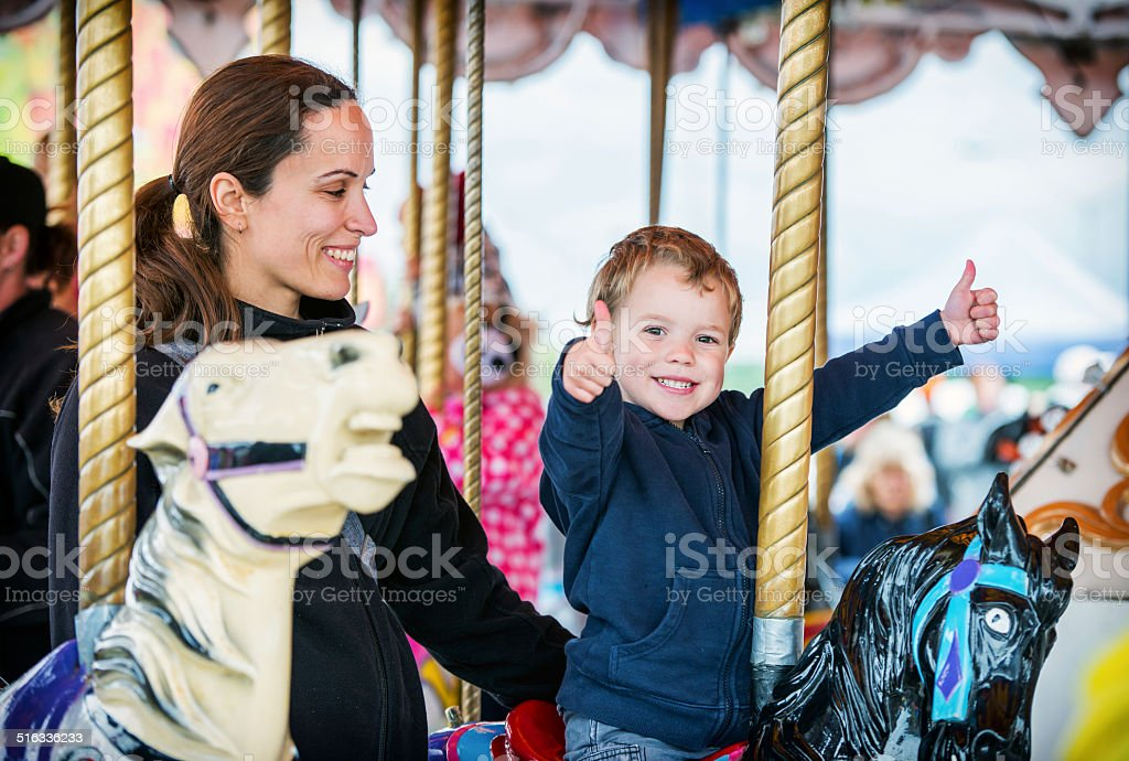 Boy with Two Thumbs Up with Mother on Carousel stock photo