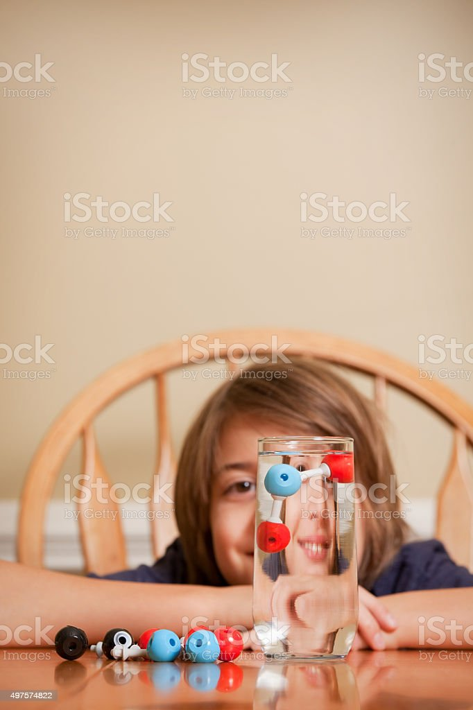 Boy With Water Molecule Model Floating In Glass stock photo