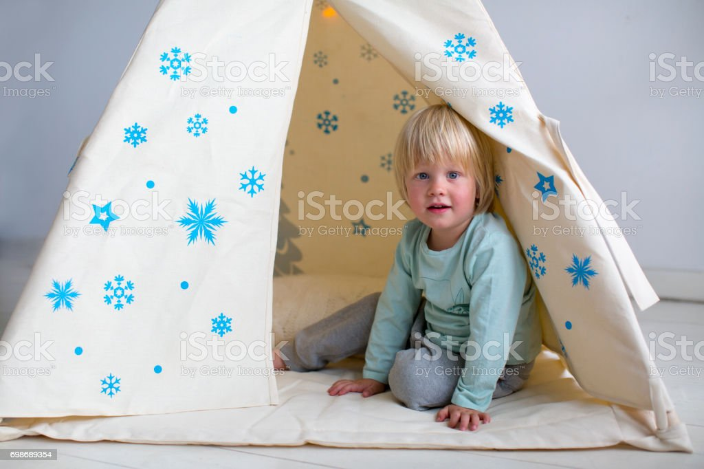 A boy with white hair is sitting in a tepee stock photo