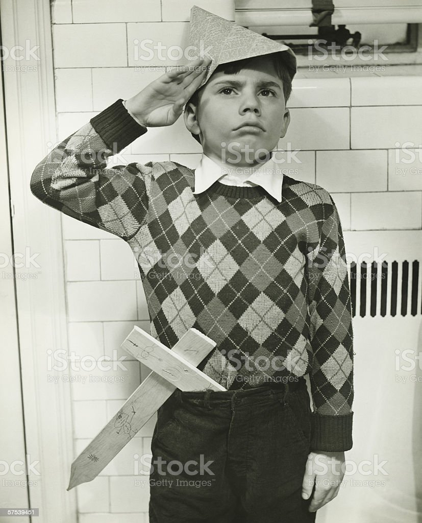 Boy (8-9) with wooden sword saluting indoors, (B&W) royalty-free stock photo