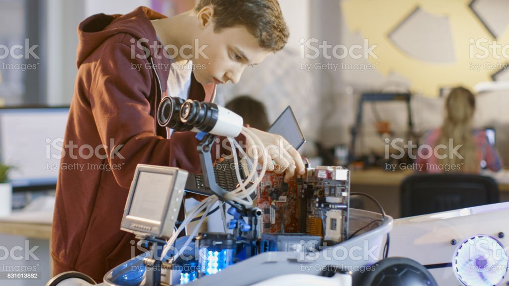 Boy Works on a Fully Functional Programable Robot with Bright LED Lights for His School Robotics Club Project. stock photo