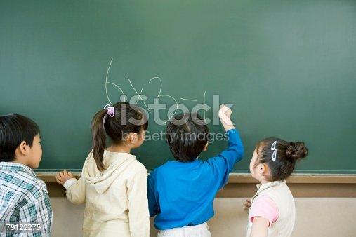 istock A boy writing a sum on a blackboard 79122275