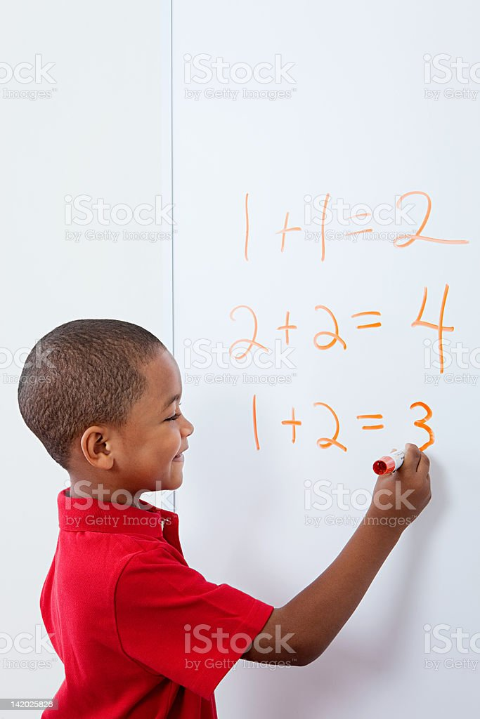 Boy writing answers to sums on whiteboard stock photo