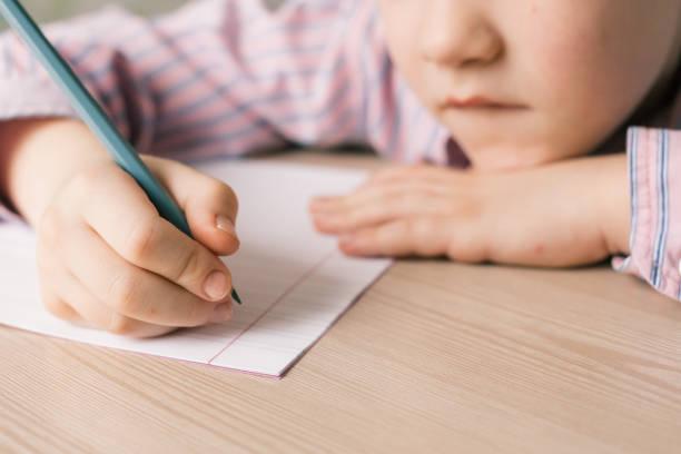 boy writing in notebook - alfabeto foto e immagini stock