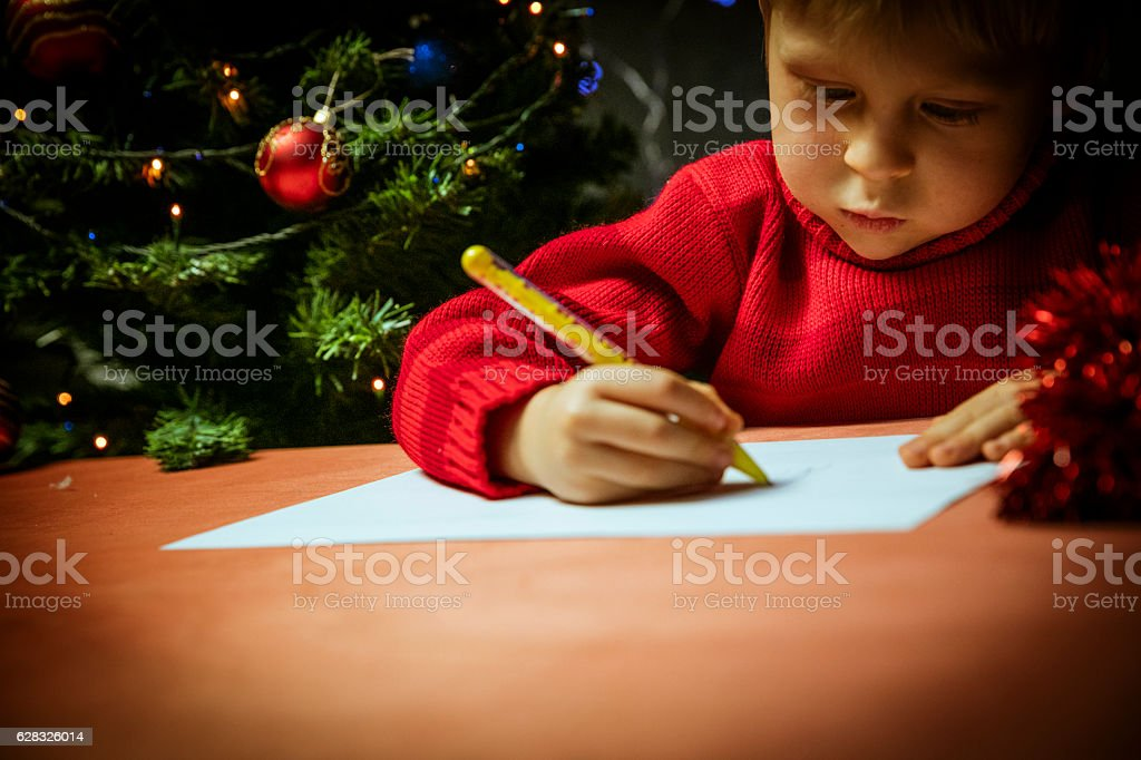 Boy writing letter to Santa stock photo