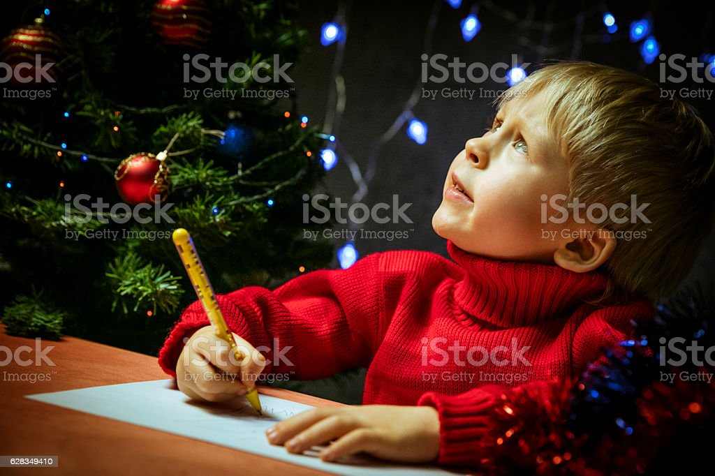 Boy writing letter to Santa stock photo