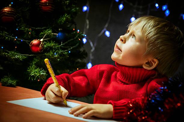 boy writing letter to santa - weihnachts wunschliste stock-fotos und bilder