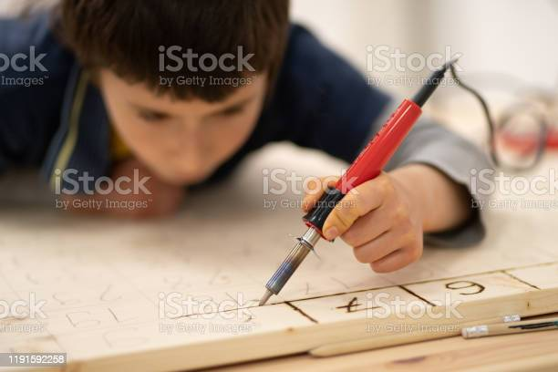 Photo of Boy writing numbers on wooden board