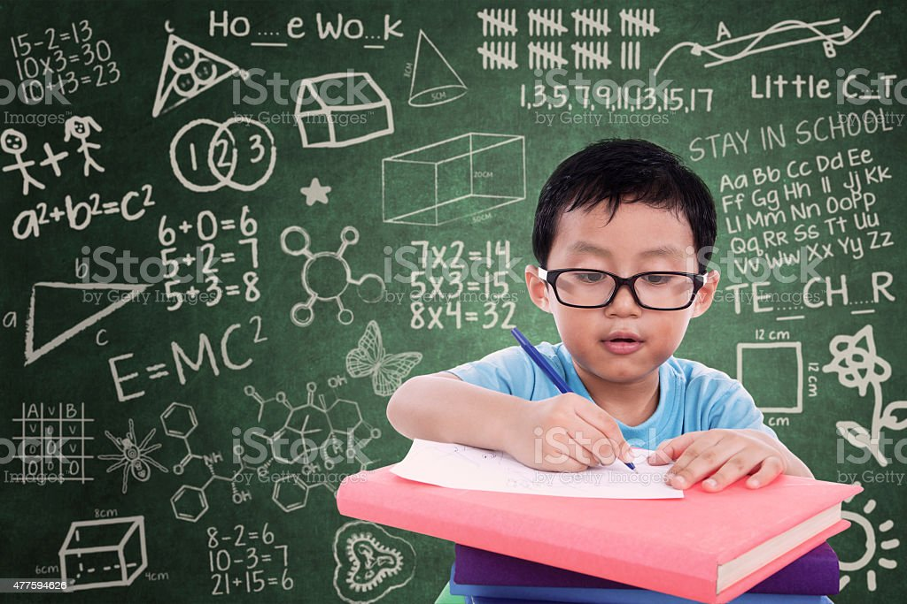 Boy writing on book in classroom stock photo
