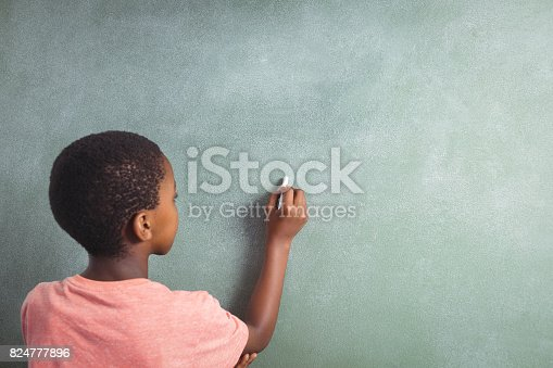 istock Boy writing with chalk on greenboard in school 824777896