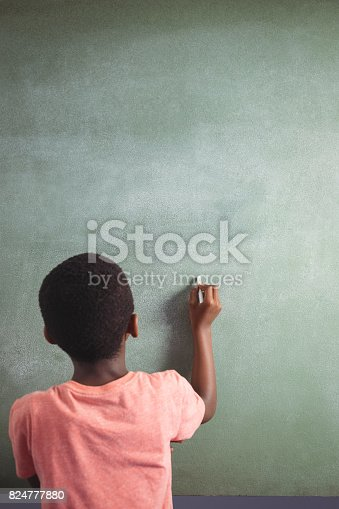 istock Boy writing with chalk on greenboard 824777880