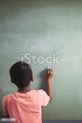 istock Boy writing with chalk on greenboard 824777880